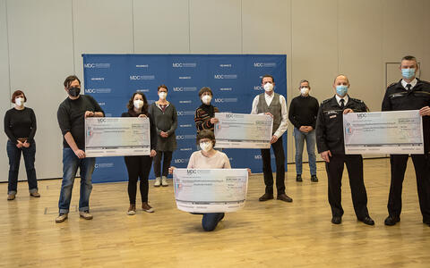 Group picture of the participants. Recipients hold checks in the air.